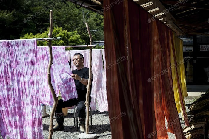 Japanese man sitting outside a textile plant dye workshop, hanging up freshly dyed pink fabric.