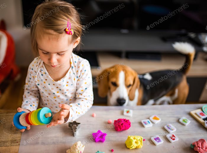 Happy little child, adorable creative 2 year old girl playing with dough, colorful modeling compound