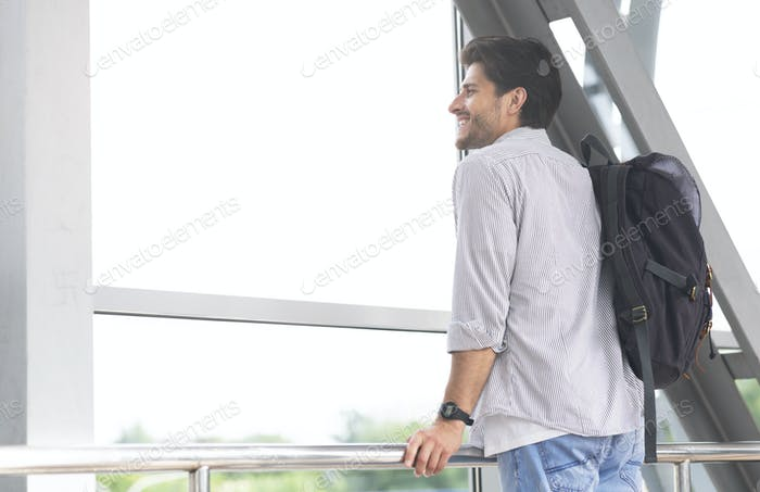 Happy tourist looking at airport window at new location