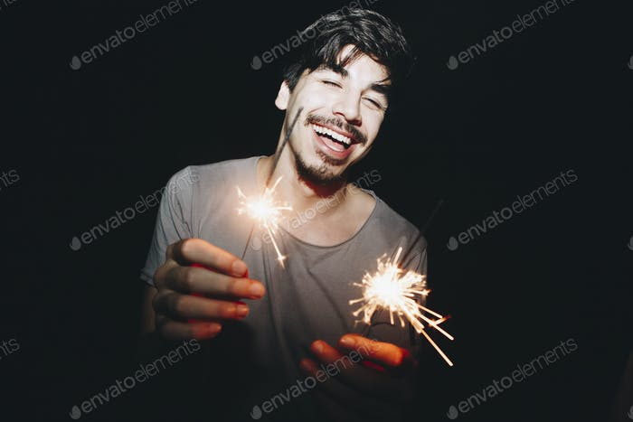 Caucasian man playing with sparklers celebration and festive party concept