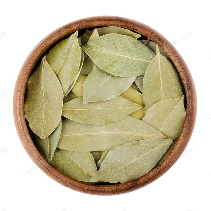 Dried bay leaves in a bowl on white