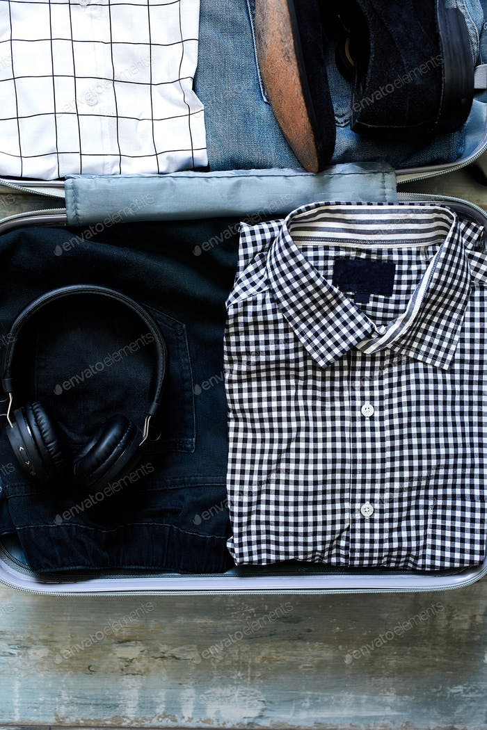 Packing suitcase at home with casual man items, stuff