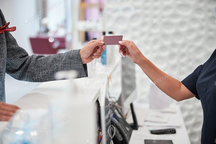 Shop assistant giving the customer a gift card