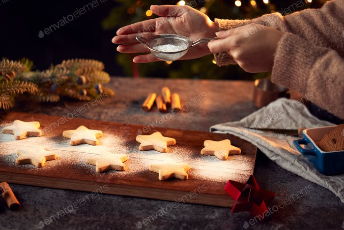 Hand Shaking Icing Sugar Over Baked Star Shaped Christmas Cookies On Board Ready For Decoration