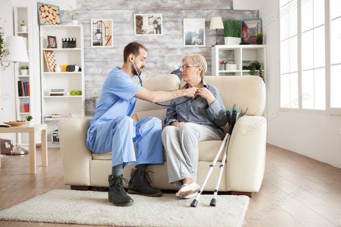 Врач со стетоскопом в доме престарелых