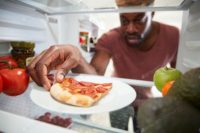 Blick aus dem Inneren des Kühlschranks als Mann öffnet Tür für übrig gebliebenen Pizza Scheibe zum Mitnehmen