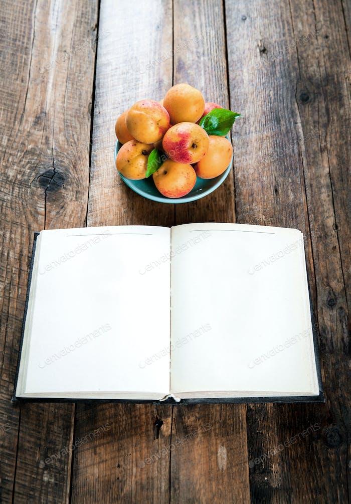 leckere Früchte. Aprikosen mit einem Buch auf einem hölzernen Hintergrund
