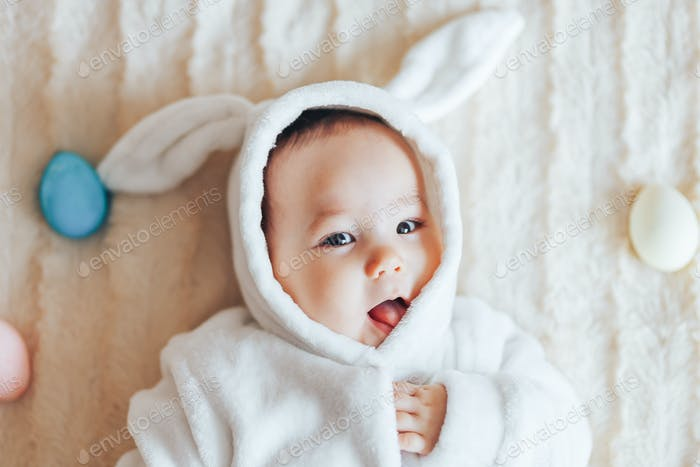 asian baby in rabbit white costume play with eggs at home