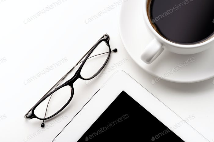 White tablet, coffee cup and glasses on a white table