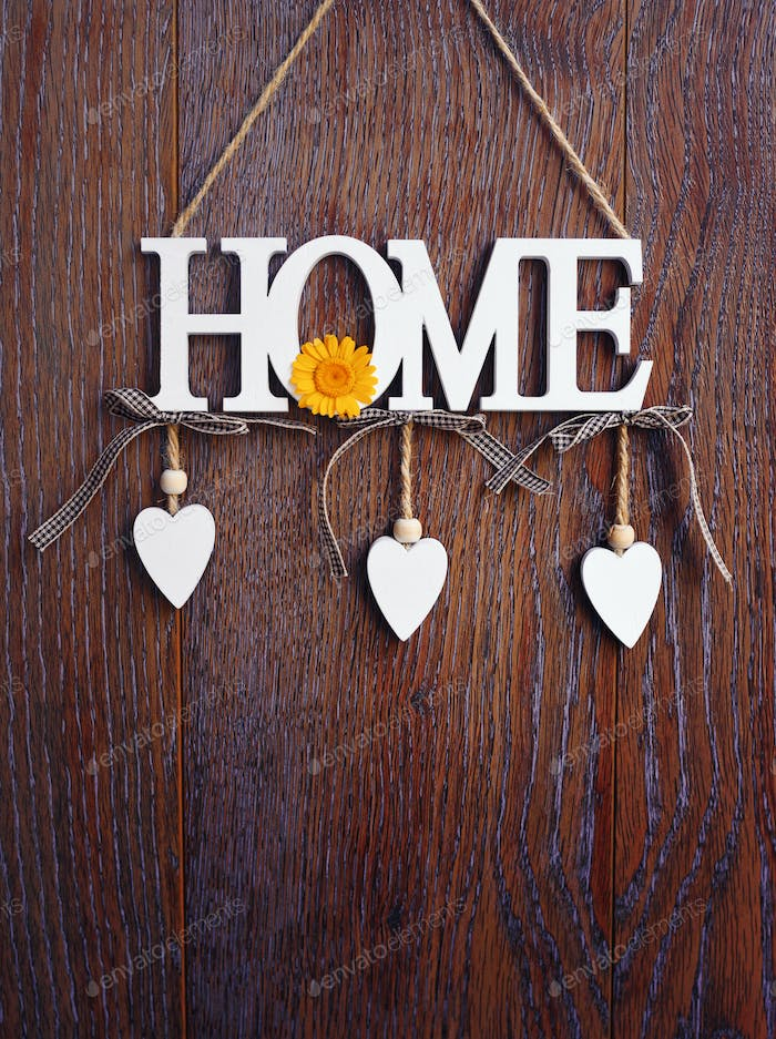 Word HOME, white letters with hearts on vintage board background