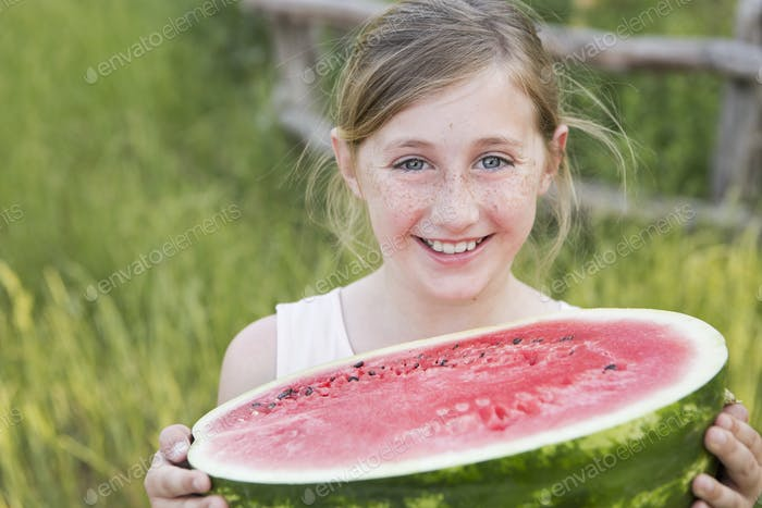 Ein Kind hält eine halbe Süßwassermelone.