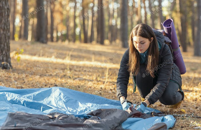 Girl backpacker setting up tent, forest background