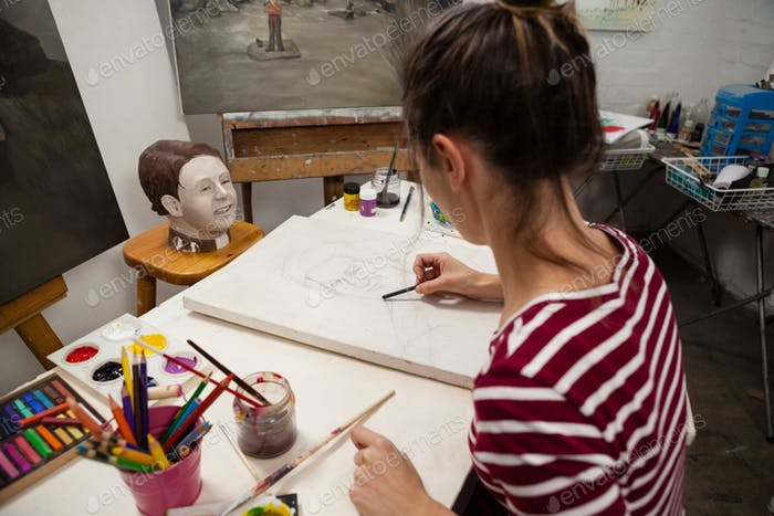 Woman sketching on canvas in drawing class