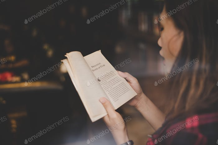 Young charming woman reading book sitting indoor in cafe. Casual portrait of teenage girl.