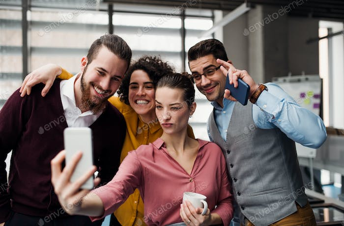 A group of young businesspeople with smartphone in office, taking selfie.