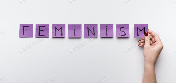 Word FEMINISM written on purple office stickers