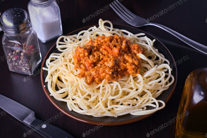 plate of cooked spaghetti with tomato sauce and minced meat on classic wooden background