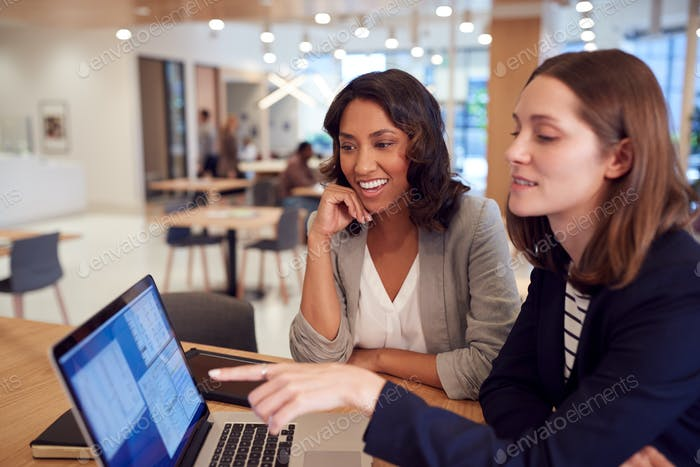 Two Businesswomen With Laptop At Desk In Open Plan Office Collaborating On Project Together