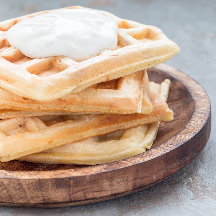 Homemade savory belgian waffles with bacon and shredded cheese on a wooden plate, square
