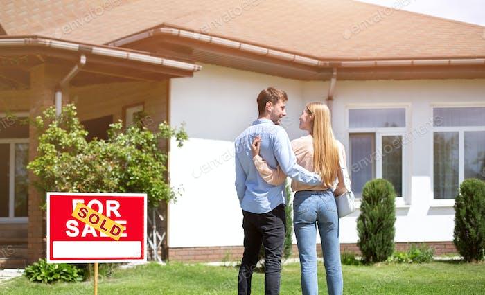 Новобрачная пара, стоящая во дворе своей новой жилой недвижимости, пустое пространство