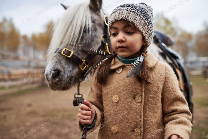 Pretty Little Girl Leading Pony By Bridle