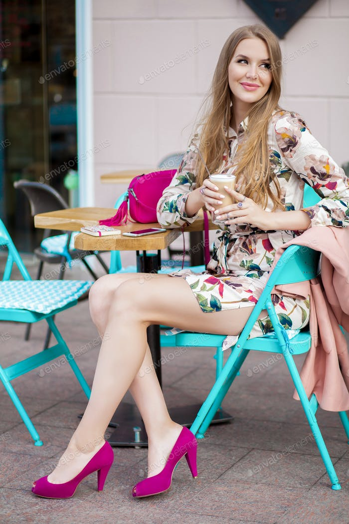 young hipster stylish woman sitting in cafe, spring summer fashion trend, drinking coffee