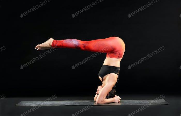 Muskulöse Frau tun einen Kopfstand mit Hecht Beine