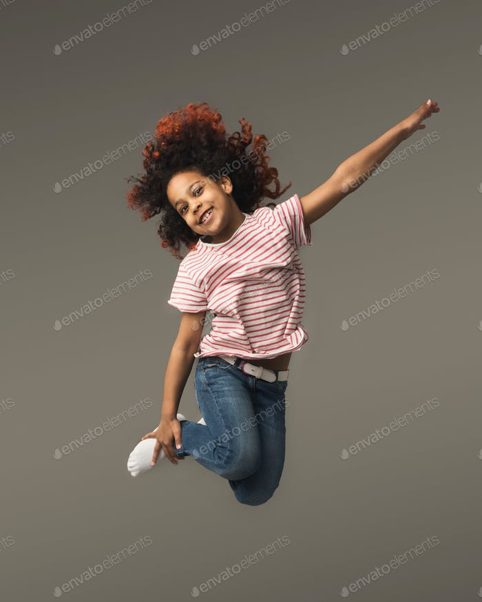 Happy little black girl jumping at studio background