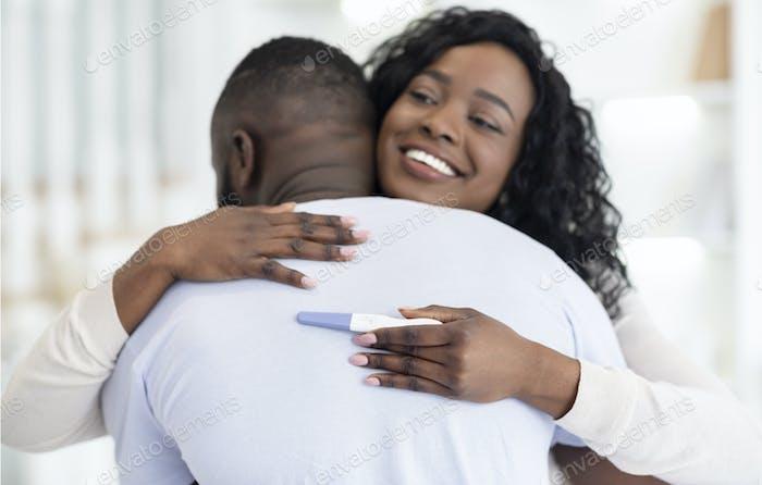 Paar glücklich über Schwangerschaft Testergebnis, umarmt einander