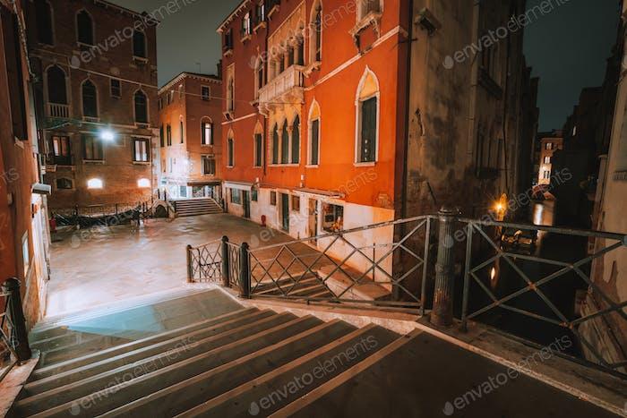 Gotisches Viertel mit alten roten Ziegelmauern in der Nacht. Leere Gassen und Brückentreppen in Venedig