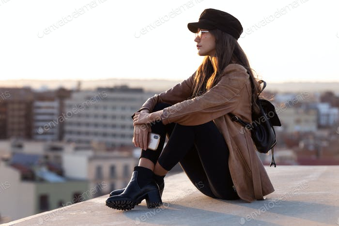 Pretty young woman enjoying time and sunset while sitting on the rooftop.