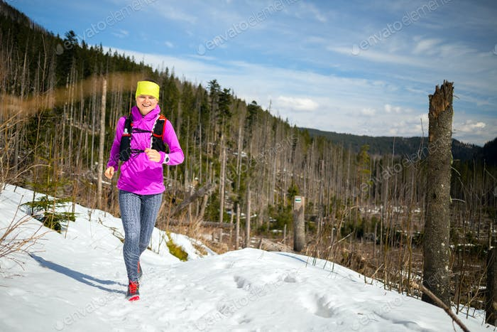 Woman winter trail running in mountains on snow