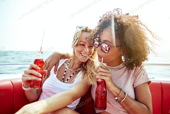Two young female friends relaxing on a boat with drinks