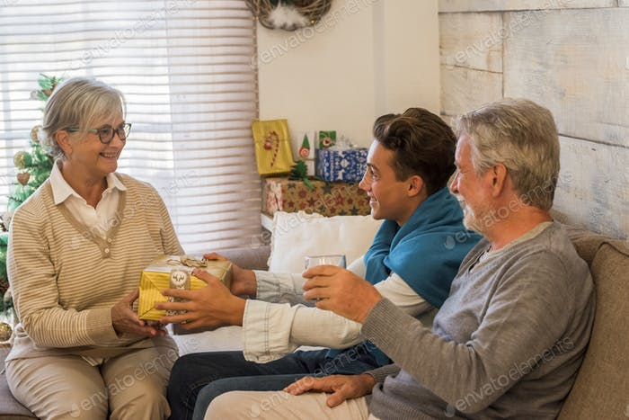 Grandparents and grandson at home celebrating christmas