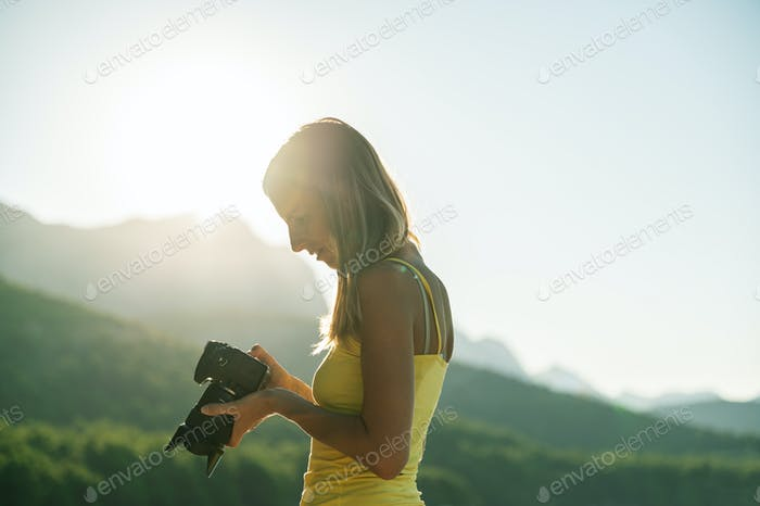 Woman photographer checking photo on camera display