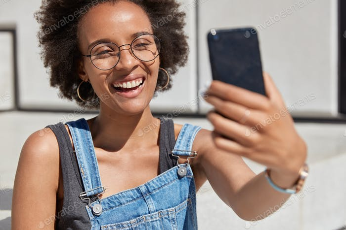 Close up shot of happy African American woman holds cellular in front, smiles broadly, takes selfie