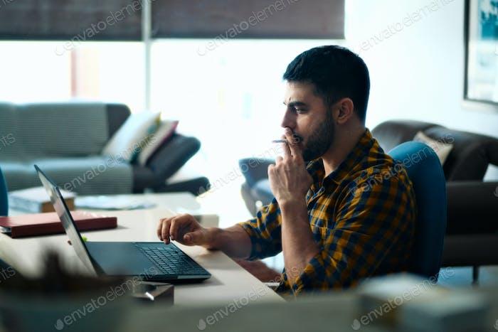 Mann arbeiten von zu Hause und rauchen Zigarette