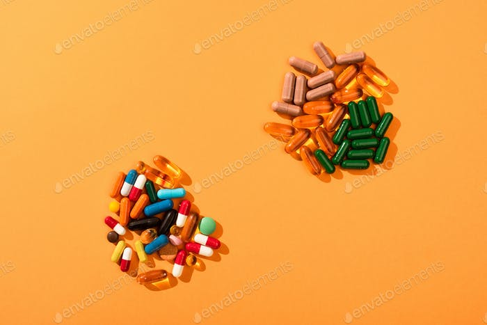 Top View of Colorful Pills And Capsules on Orange Background