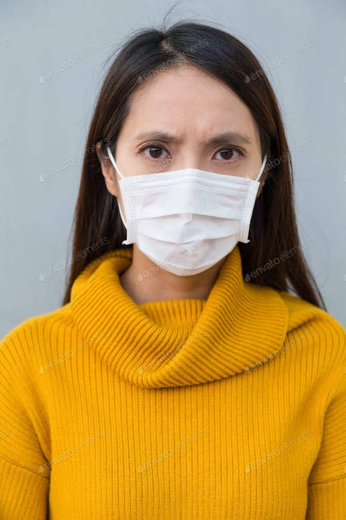 Frau fühlt sich unwohl und trägt Gesichtsmaske
