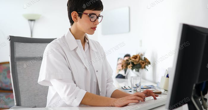Charming female doctor typing on a keyboard