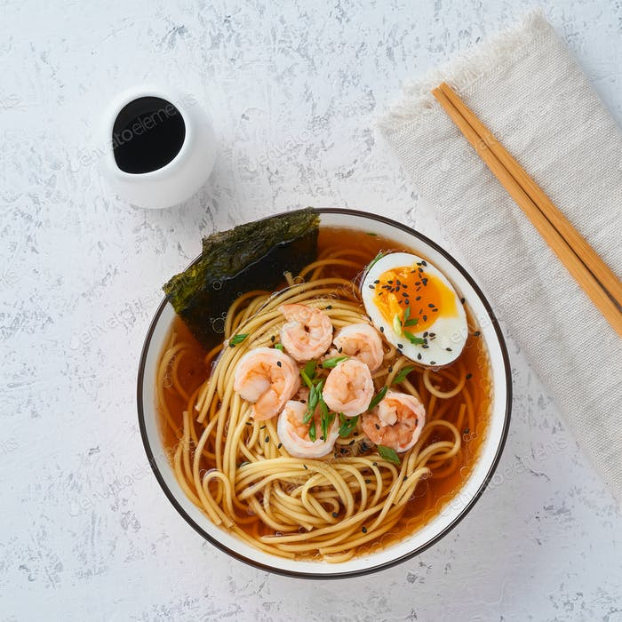 Asian soup with noodles, ramen with shrimps. White stone table, top view
