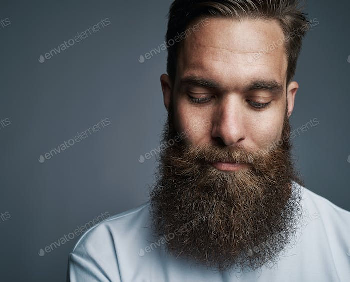 Young man with a long beard deep in thought