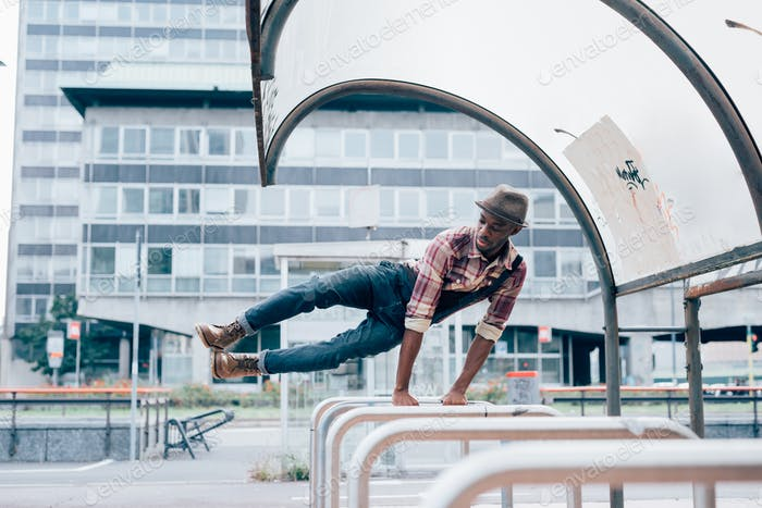 Filtered young handsome afro black man jumping leaning his hand