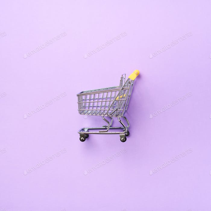 Shopping cart on purple background. Minimalism style. Square crop. Creative design. Top view with