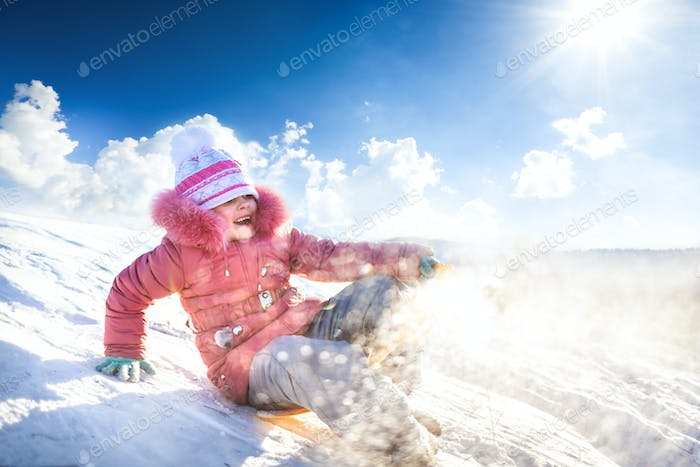 Happy girl sledding outdoors on clear winter day