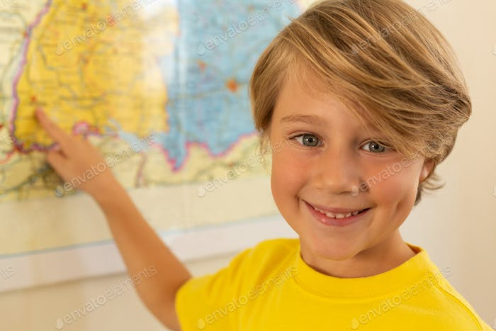 Happy boy looking at camera and pointing with his finger on a map in classroom at elementary school