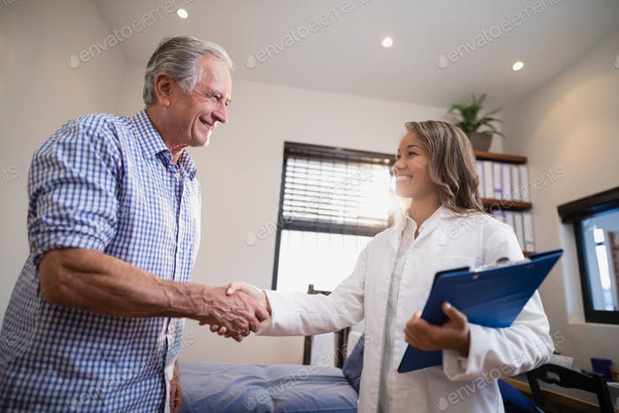 Smiling senior male patient and female therapist shaking hands