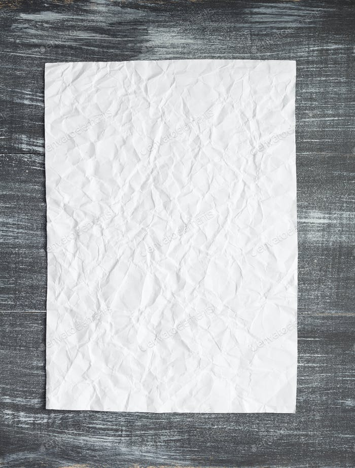 empty white wrinkled paper at wood
