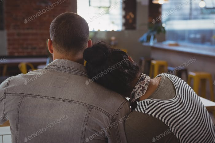 Woman leaning on man shoulder in cafe
