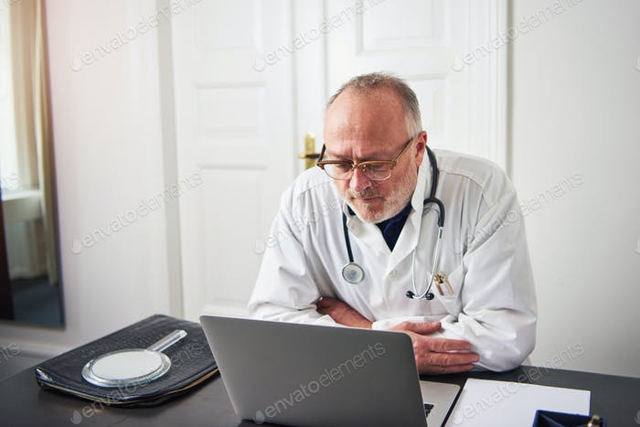 Adult thoughtful medic sitting in office and looking at laptop